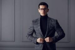 L'uomo degli affari sicuro e bello in occhiali neri, il collo alto nero ed il rivestimento grigio del plaid esamina seri la macch fotografie stock