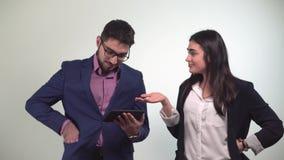 L'uomo dei colleghi di ufficio esamina la compressa e la ragazza dopo che il ballo ottiene la carta di credito vinta nella scomme stock footage