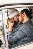 L'uomo dei pantaloni a vita bassa e la donna bei di bellezza si baciano che si siede nella retro automobile Concetto di giorno de Fotografia Stock