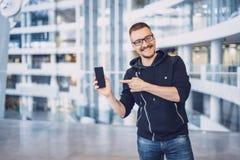L'uomo dei pantaloni a vita bassa indica sul telefono cellulare fotografia stock