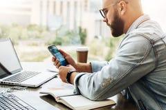 L'uomo dei pantaloni a vita bassa si siede in caffè, utilizza lo smartphone, lavora a due computer portatili L'uomo d'affari legg fotografie stock
