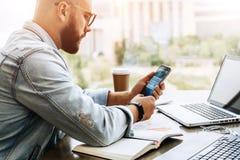 L'uomo dei pantaloni a vita bassa si siede in caffè, utilizza lo smartphone, lavora a due computer portatili L'uomo d'affari legg fotografia stock