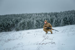 L'uomo del cacciatore si è vestito in abbigliamento del cammuffamento che sta nell'inverno Fotografia Stock