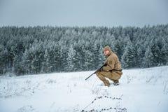L'uomo del cacciatore si è vestito in abbigliamento del cammuffamento che sta nell'inverno Immagine Stock