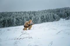 L'uomo del cacciatore si è vestito in abbigliamento del cammuffamento che sta nell'inverno Fotografie Stock Libere da Diritti