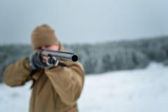 L'uomo del cacciatore si è vestito in abbigliamento del cammuffamento che sta nell'inverno Fotografie Stock