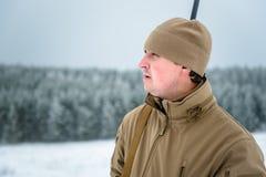 L'uomo del cacciatore si è vestito in abbigliamento del cammuffamento che sta nell'inverno Immagini Stock