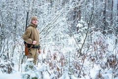 L'uomo del cacciatore si è vestito in abbigliamento del cammuffamento che sta nell'inverno Fotografia Stock Libera da Diritti