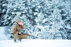 L'uomo del cacciatore si è vestito in abbigliamento del cammuffamento che sta nell'inverno Immagine Stock Libera da Diritti
