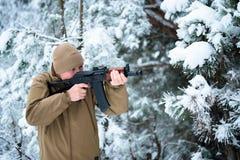 L'uomo del cacciatore si è vestito in abbigliamento del cammuffamento che sta nell'inverno Immagini Stock Libere da Diritti