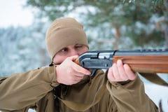 L'uomo del cacciatore si è vestito in abbigliamento del cammuffamento nel pino FO dell'inverno Immagini Stock Libere da Diritti