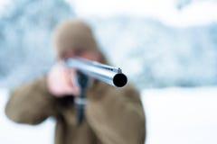 L'uomo del cacciatore si è vestito in abbigliamento del cammuffamento nel pino FO dell'inverno Fotografia Stock