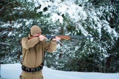 L'uomo del cacciatore si è vestito in abbigliamento del cammuffamento nel pino FO dell'inverno Fotografia Stock Libera da Diritti