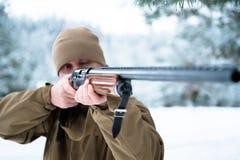 L'uomo del cacciatore si è vestito in abbigliamento del cammuffamento nel pino FO dell'inverno Immagine Stock