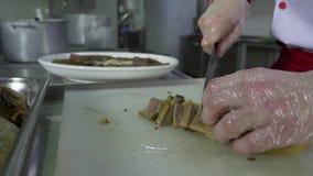 L'uomo del cuoco taglia la carne cotta su una tavola di taglio video d archivio