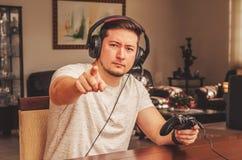 L'uomo del Gamer che indica il dito sta sfidando lo spettatore t Immagini Stock