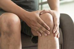 l'uomo del ginocchio tiene sulla sofferenza dal dolore in primo piano del ginocchio La L Immagini Stock