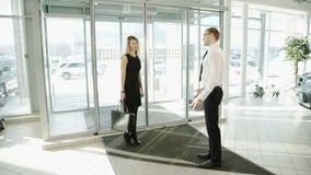 L'uomo del lavoratore nel centro automobilistico incontra il cliente della donna per visualizzare le automobili archivi video