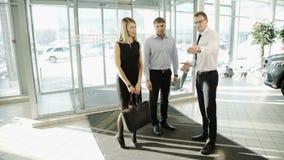 L'uomo del lavoratore nel centro automobilistico incontra il cliente delle coppie per visualizzare le automobili archivi video