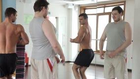 l'uomo del maritino ed il culturista dell'atleta li esaminano nello specchio nella palestra stock footage
