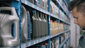 L'uomo del meccanico di automobile sceglie l'olio di motore per l'automobile al supermercato del distributore di benzina della ri archivi video