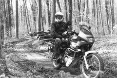L'uomo del motociclista sta sedendosi sulla motocicletta di avventura Fuori dalla strada Viaggio del motociclo enduro che viaggia immagini stock libere da diritti