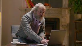 L'uomo del pensionato scrive con un dito sul computer portatile e si siede in suo cottage caldo del paese stock footage