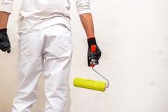 L'uomo del pittore sul lavoro con un rullo di pittura esamina la parete immagine stock