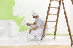 L'uomo del pittore sul lavoro prende il colore con il rullo di pittura dalla b immagini stock