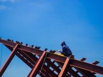 L'uomo del saldatore una saldatura il tetto d'acciaio, lavoratore con sprotetto fotografie stock