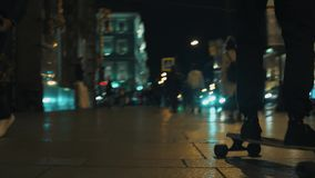 L'uomo del skateboarder in maglia con cappuccio nera guida sul foo ammucchiato della città di notte stock footage