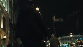 L'uomo del skateboarder in maglia con cappuccio nera guida sul marciapiede ammucchiato della città di notte archivi video