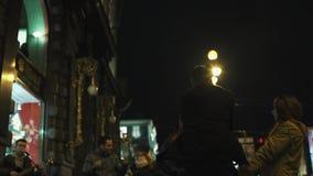 L'uomo del skateboarder in maglia con cappuccio nera guida sulla pavimentazione ammucchiata della città di notte video d archivio