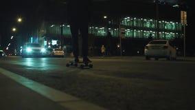 L'uomo del skateboarder in maglia con cappuccio nera guida sulla strada di città di notte vicino al centro di affari stock footage