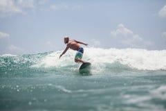L'uomo del surfista che pratica il surfing sulle onde spruzza attivamente Fotografia Stock Libera da Diritti