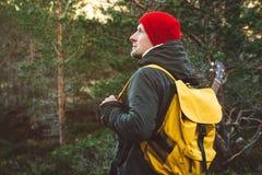 L'uomo del viaggiatore sta stando su una traccia in mezzo ad una foresta con una chitarra Uso dello zaino giallo in un cappello r fotografie stock