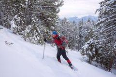 L'uomo del viaggiatore va a snowshoeing in salita Immagine Stock