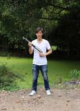 L'uomo dell'artigliere che tiene pistola lunga nelle mani e nella destra girata oblique con il tralicco bianco del denim e della  fotografie stock libere da diritti