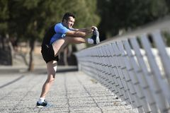 L'uomo dell'atleta che allunga le gambe che si scaldano il vitello muscles prima dell'allenamento corrente che si appoggia il par Fotografie Stock Libere da Diritti