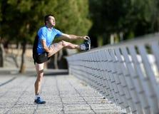 L'uomo dell'atleta che allunga le gambe che si scaldano il vitello muscles prima dell'allenamento corrente che si appoggia il par Fotografia Stock