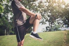 L'uomo dell'atleta che fa un certo allungamento esercita le gambe prima di correre Immagini Stock Libere da Diritti
