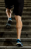 L'uomo dell'atleta con la forte gamba muscles la scala urbana della città di funzionamento e di addestramento nella forma fisica  Immagine Stock