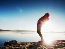 L'uomo dell'atleta sta piegando indietro Pieghi ed allunghi i muscoli dorsali all'interno del pareggiare di mattina Fotografia Stock