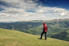 L'uomo dell'avventuriere con una mappa sta camminando nelle montagne Fotografia Stock