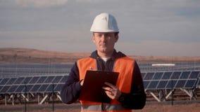 L'uomo dell'ingegnere in un casco bianco ed in una maglia arancio, qualcosa nota e fa uno schizzo della matita nel campo di solar stock footage