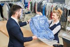 L'uomo della lavanderia del lavoratore della ragazza dà al cliente i vestiti puliti Fotografia Stock