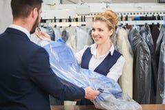 L'uomo della lavanderia del lavoratore della ragazza dà al cliente i vestiti puliti Immagine Stock Libera da Diritti