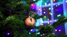 L'uomo della mano che decora sull'albero di Natale con incandescenza di Natale si accende stock footage