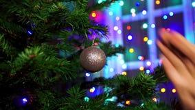 L'uomo della mano che decora sull'albero di Natale con incandescenza di Natale si accende archivi video
