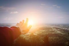 L'uomo della mano che indica con il tramonto nell'area montagnosa, si rilassa il concetto ed il viaggio fotografia stock